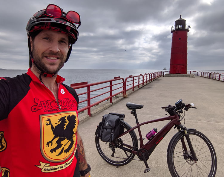 Man  in red jersey posing with his electric bike in front of a lighthouse by a lake