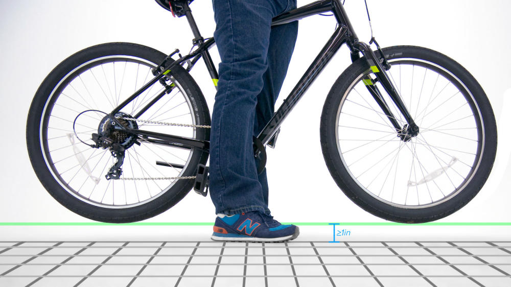 person standing over bicycle showing optimal 1 inch standover clearance