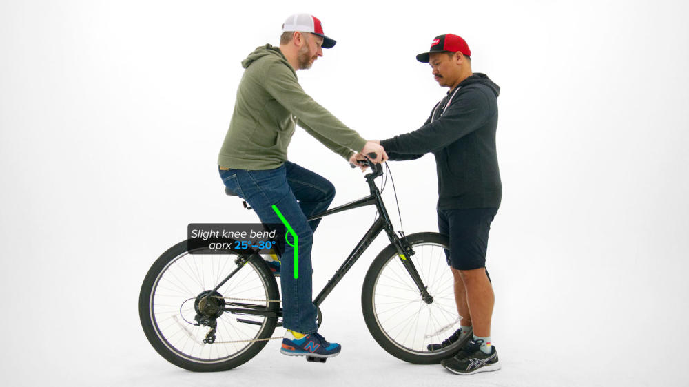 Man sitting on bicycle with another man holding handlebars to keep balance showing optimal knee bend for correct bike size