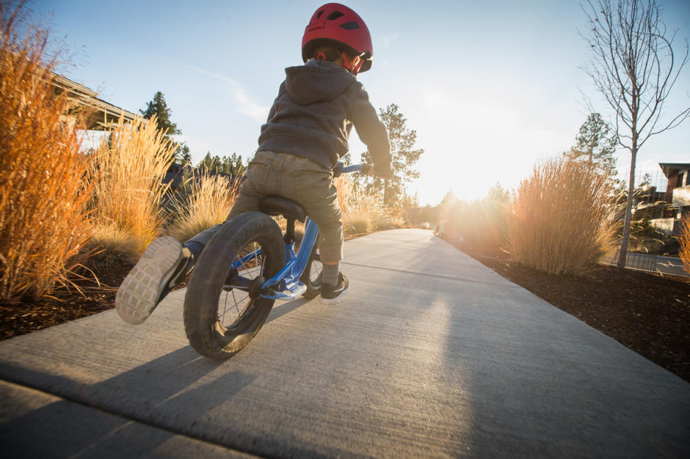 small child riding a balance bike and pushing feet into ground for momentum