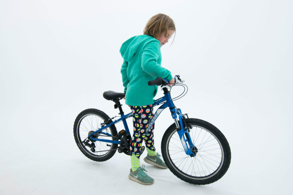 child standing over bike showing correct spacing between child and top tube