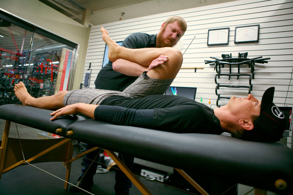 Male Body Geometry Bike Fitter stretching leg of man laying on table