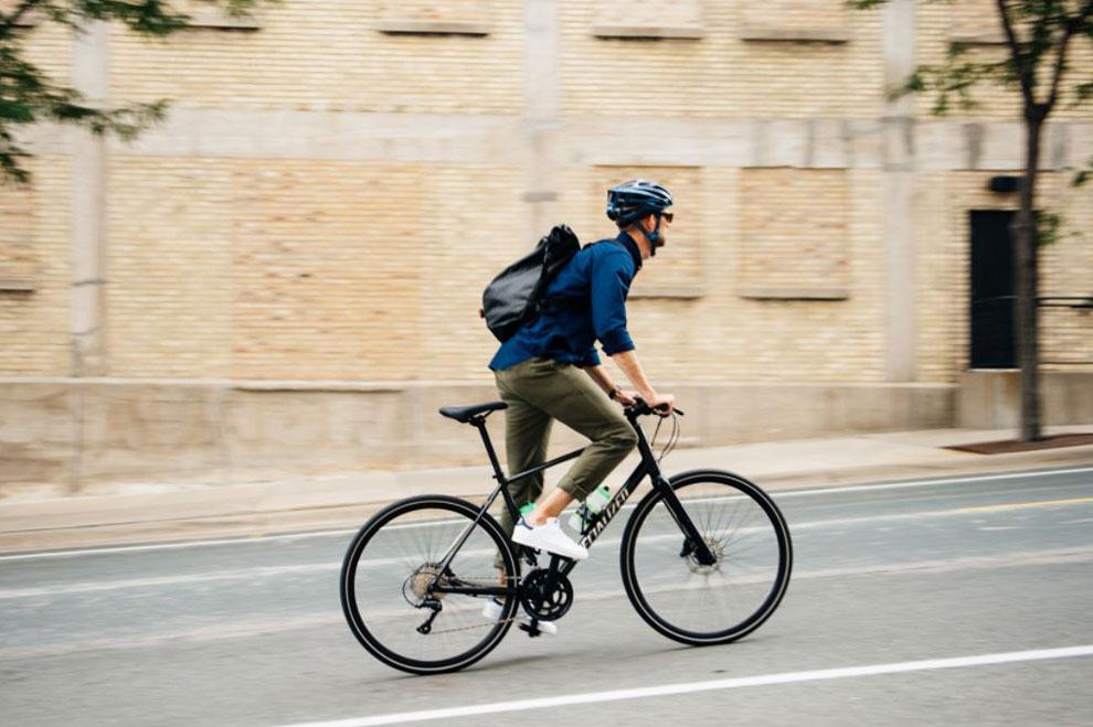 Man commuting by bike on city street wearing backpack