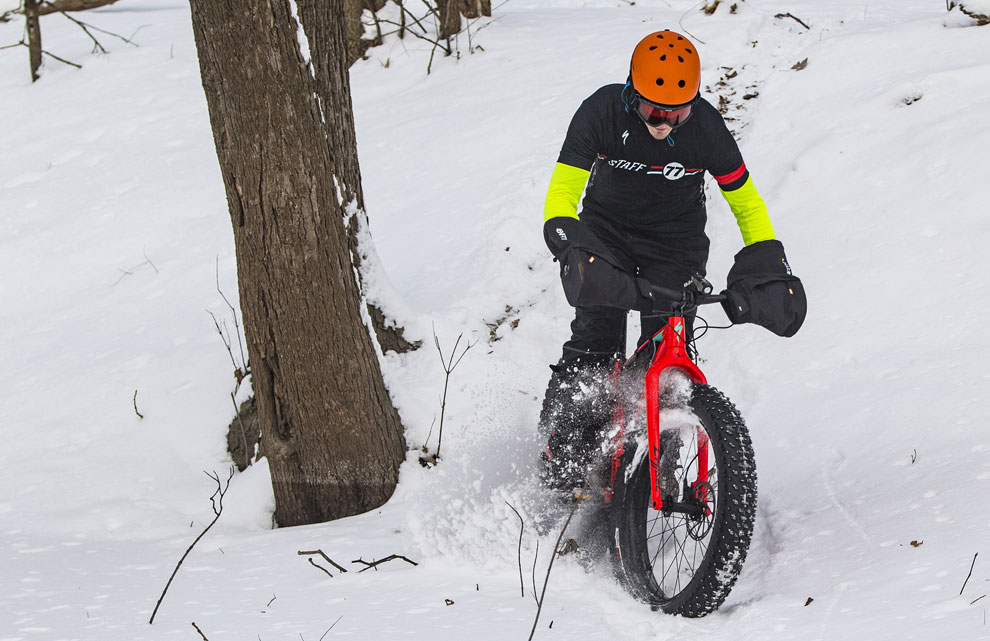 Man riding a fat mountain bike on snow through the woods