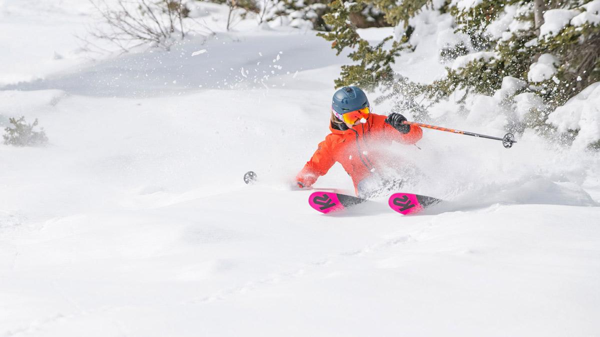 Woman downhill skiing in deep powder snow