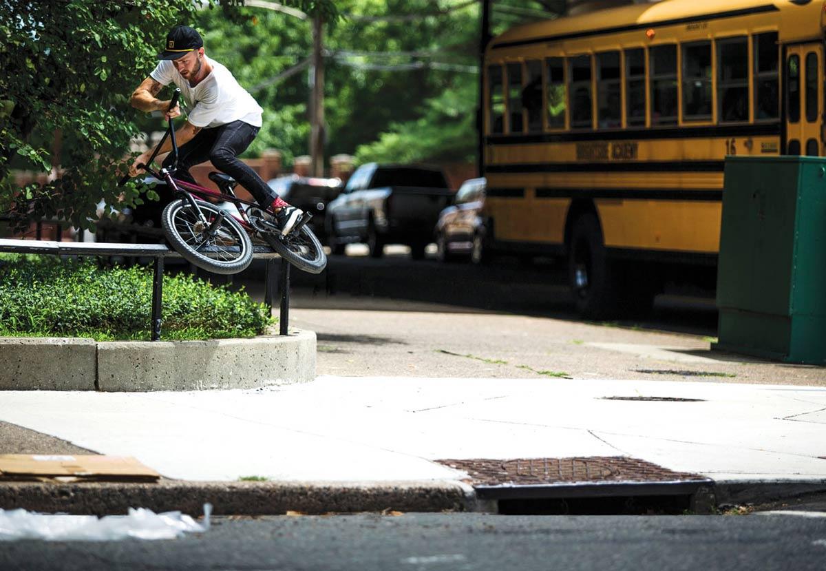 BMX Rider doing a grind on a sidewalk railing