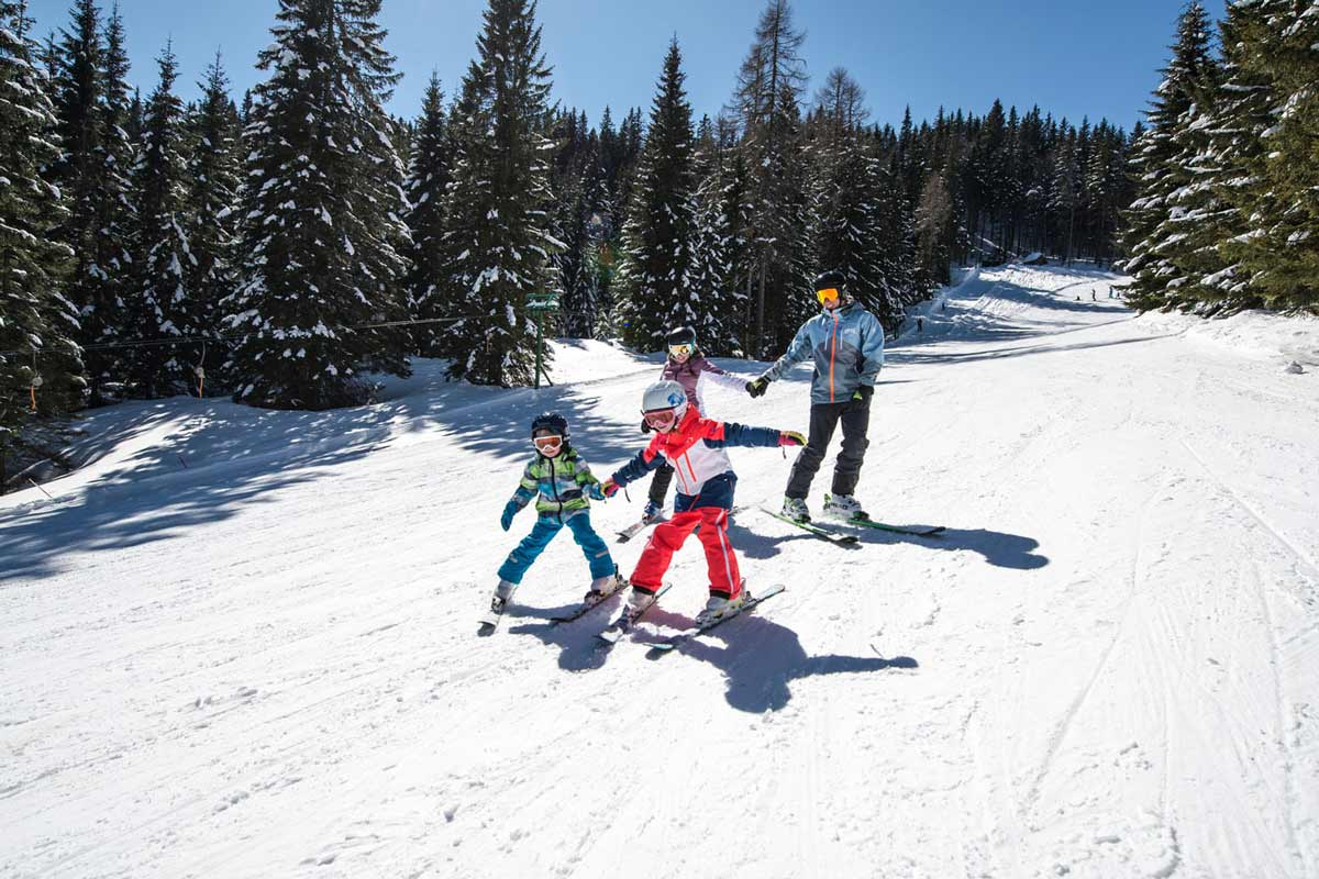 A dad with Daughters Skiing Holding Hands for Safety