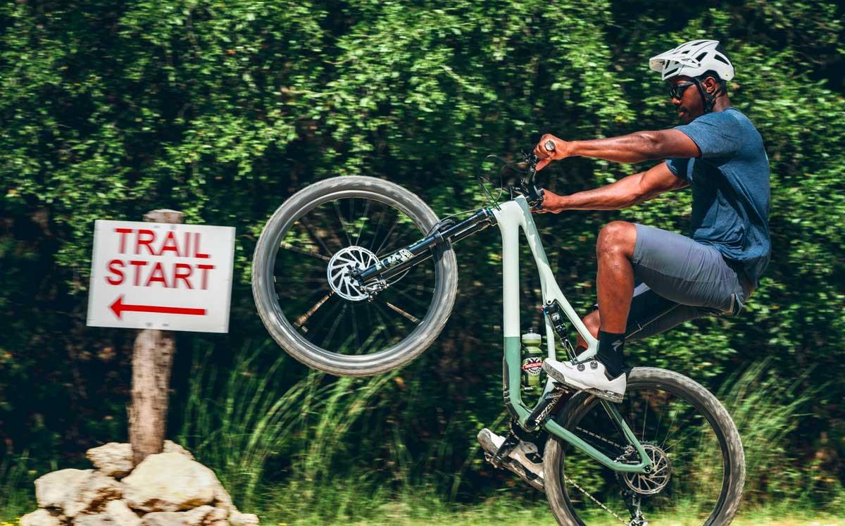 Man Doing a Wheelie Approaching a Mountain Bike Trail Entrance