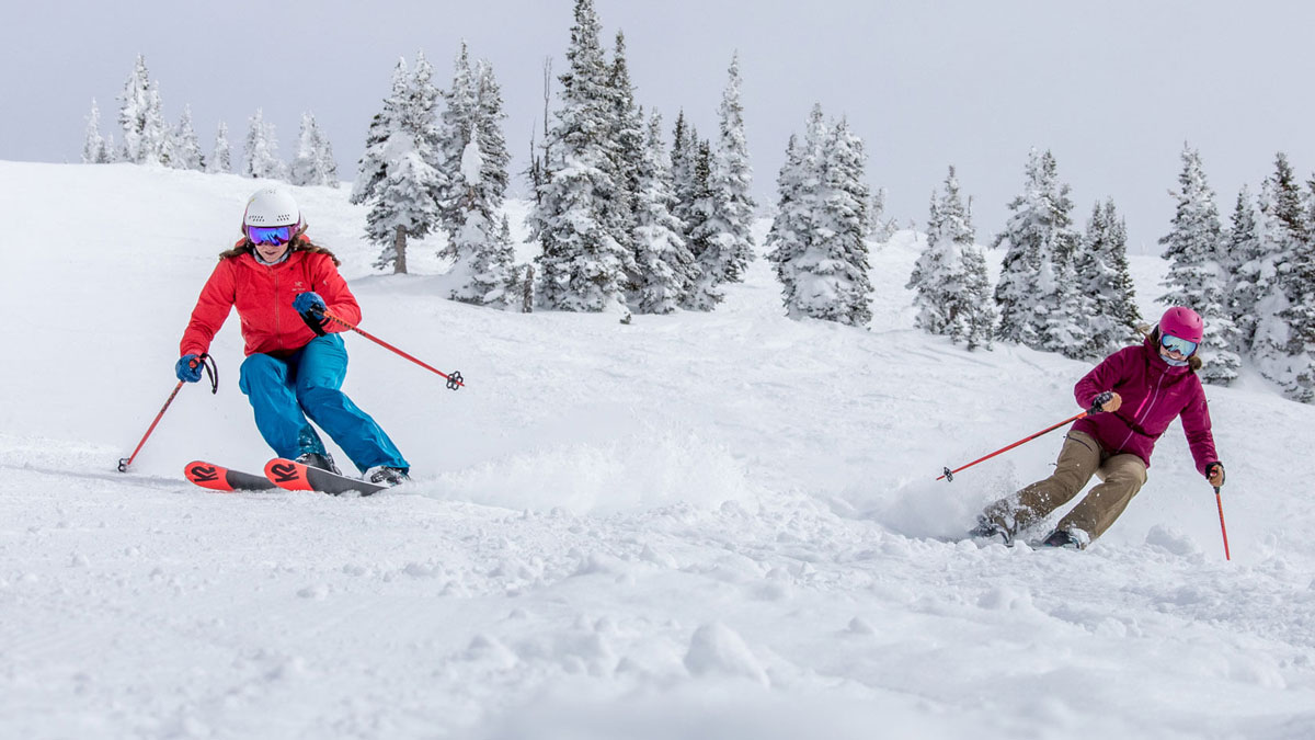 2 Women Downhill Skiing On A Snowy Hill