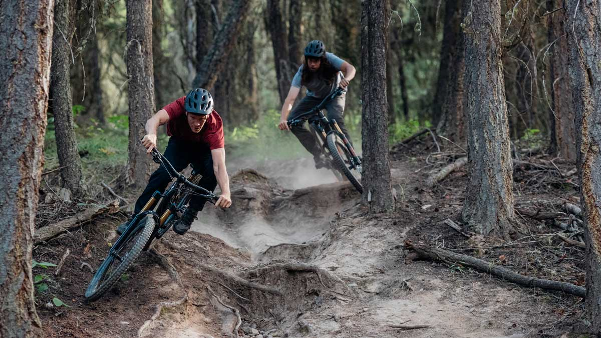 2 Men Riding Fast On Enduro Bikes In Wooded Trail