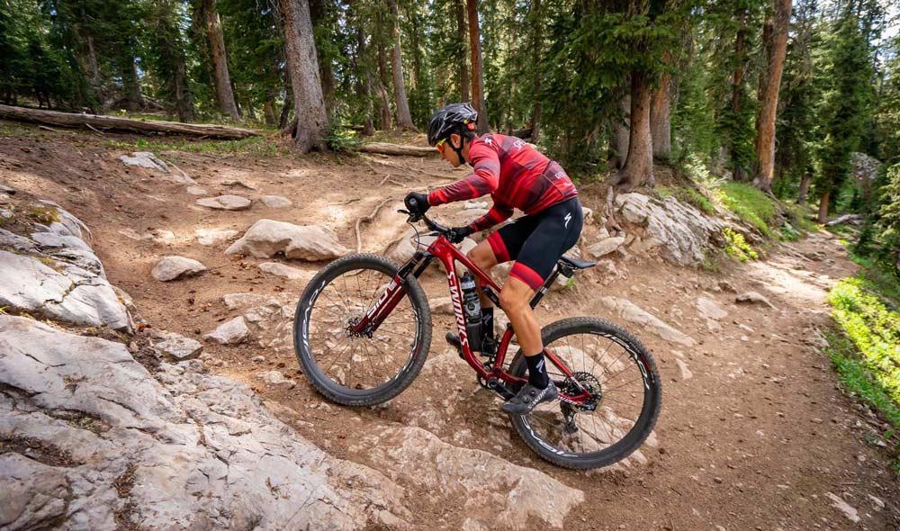 Man Racing a Cross-Country Mountain Bike on a Rocky Trail