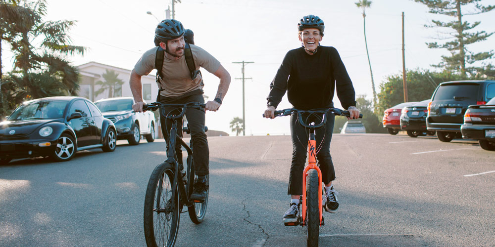 a man and woman riding Specialized Roll comfort bikes on urban street
